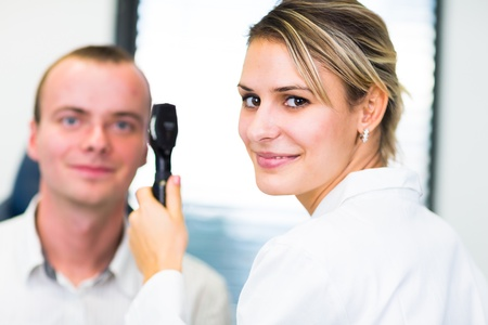 medical examination: Optometry concept - handsome young man having her eyes examined by an eye doctor