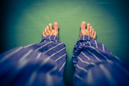Alone in the house: man in pyjamas looking down on his  feet photo