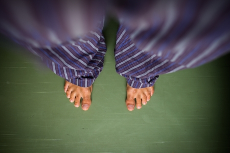 Alone in the house: man in pyjamas looking down on his bare feet Stock Photo - 16818550