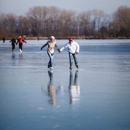 ice skating: Couple ice skating outdoors on a pond on a lovely sunny winter day Stock Photo