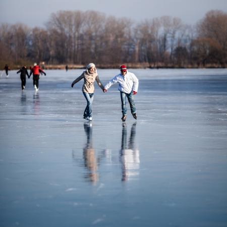 patinaje sobre hielo: Patinaje sobre hielo al aire libre Pareja en un estanque en un día soleado de invierno hermoso