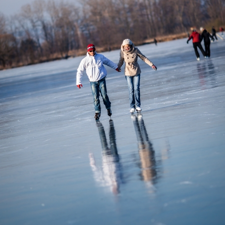 speed skating: Couple ice skating outdoors on a pond on a lovely sunny winter day Stock Photo