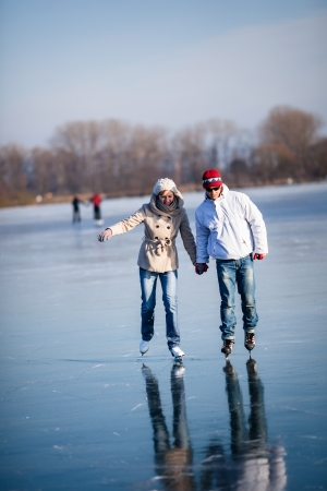 ice water: Couple ice skating outdoors on a pond on a lovely sunny winter day Stock Photo