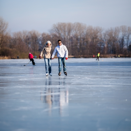 Couple ice skating outdoors on a pond on a lovely sunny winter day Stock Photo - 17030340