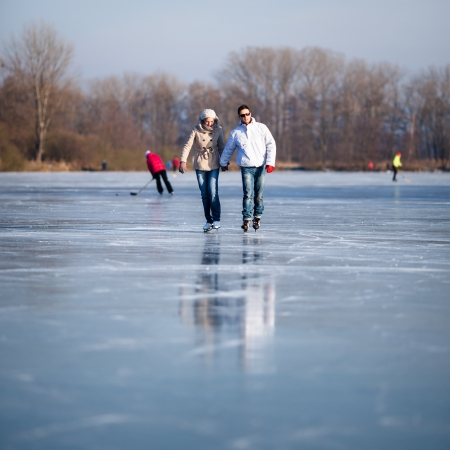 Couple ice skating outdoors on a pond on a lovely sunny winter day Stock Photo - 17030333