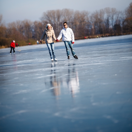 Couple ice skating outdoors on a pond on a lovely sunny winter day Stock Photo - 17038826