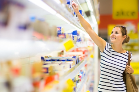 aisle: Beautiful young woman shopping for diary products at a grocery storesupermarket (color toned image)