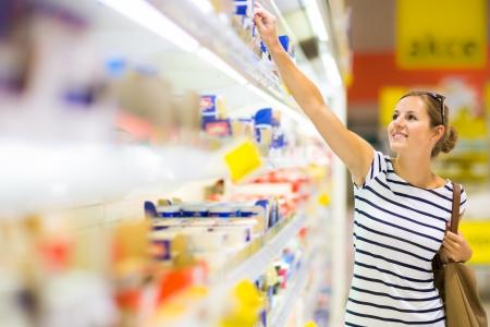 abarrotes: Joven y bella mujer de compras para los productos l�cteos en el supermercado  supermercado (imagen a color entonado) Foto de archivo