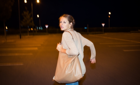 deranged: Scared young woman running from her pursuer in a deserted parking lot