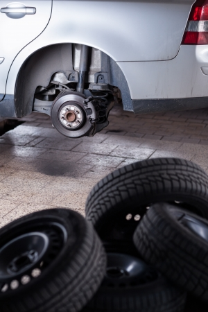 tire service: inside a garage - changing wheelstires (shallow DOF; color toned image) Stock Photo
