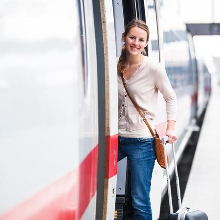 Pretty young woman boarding a train photo