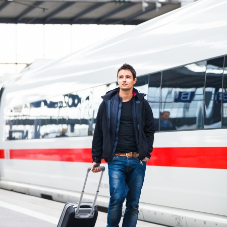 rails: Just arrived  handsome young man walking along a platform at a modern train station Stock Photo