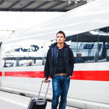 viajero: Reci�n apuesto joven caminando por un and�n de una estaci�n de tren moderno