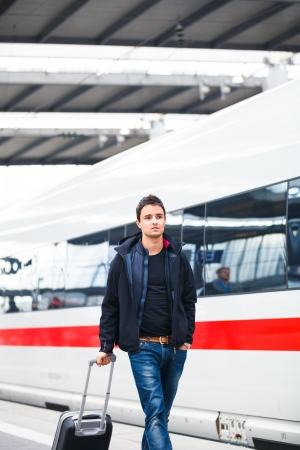 just arrived: Just arrived  handsome young man walking along a platform at a modern train station Stock Photo