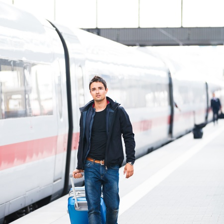 modern train: Just arrived  handsome young man walking along a platform at a modern train station Stock Photo
