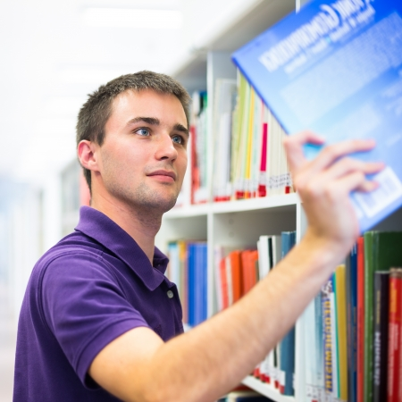 choose university: Handsome college student in library (shallow DOF; color toned image) Stock Photo