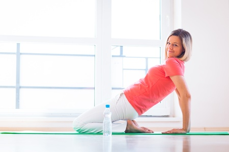 kneeling woman: Pretty young woman doing YOGA exercise at home