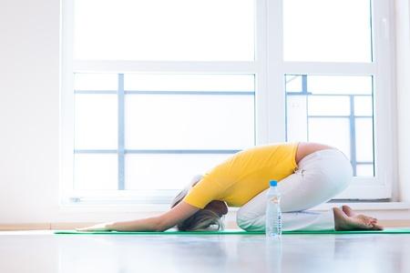 arrodillarse: Bastante joven haciendo ejercicios de yoga en casa Foto de archivo
