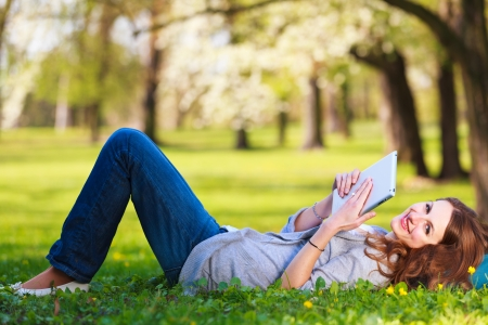 Young woman using her tablet computer while relaxing outdoors in a park on a lovely spring day photo