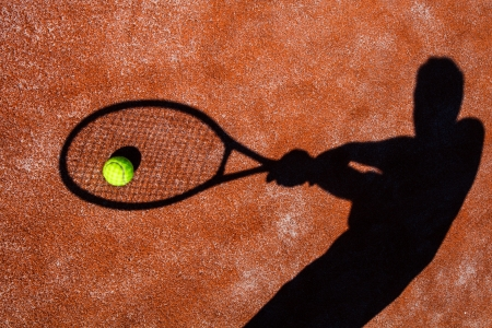 wimbledon: shadow of a tennis player in action on a tennis court (conceptual image with a tennis ball lying on the court and the shadow of the player positioned in a way he seems to be playing it)
