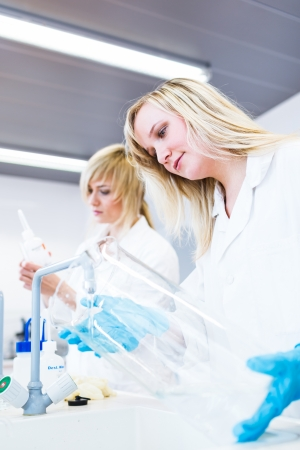 Two female researchers working in a laboratory (color toned image) photo