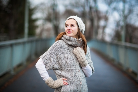 Autumnwinter portrait: young woman dressed in a warm woolen cardigan posing outside in a city park