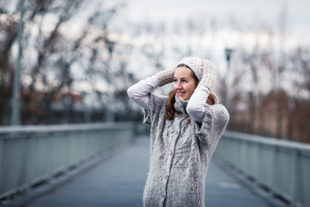 Autumn/winter portrait: young woman dressed in a warm woolen cardigan posing outside in a city park Stock Photo - 17038486