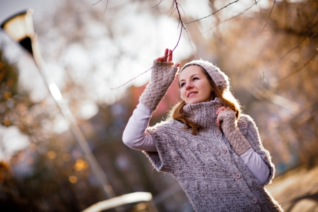 cardigan: Autumnwinter portrait: young woman dressed in a warm woolen cardigan posing outside in a city park