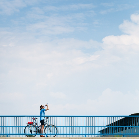pertaining: Background for poster or advertisment pertaining to cyclingsportoutdoor activities - female cyclist during a halt on a bridge against blue sky (color toned image)