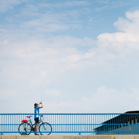 Background for poster or advertisment pertaining to cycling/sport/outdoor activities - female cyclist during a halt on a bridge against blue sky (color toned image) Stock Photo - 17038461
