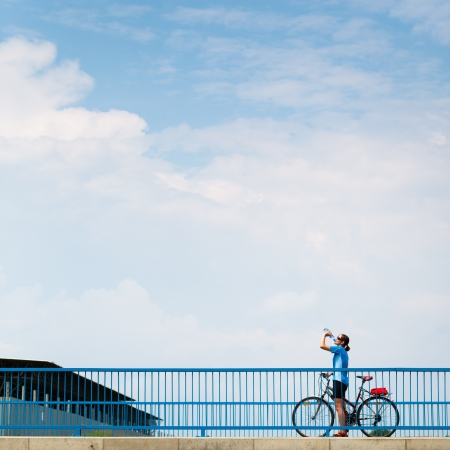 advertisment: Background for poster or advertisment pertaining to cyclingsportoutdoor activities - female cyclist during a halt on a bridge against blue sky (color toned image)
