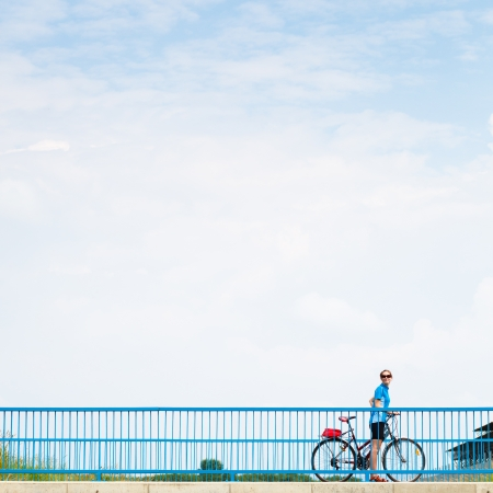 Background for poster or advertisment pertaining to cycling/sport/outdoor activities - female cyclist during a halt on a bridge against blue sky (color toned image) Stock Photo - 17040284