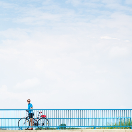 weekend break: Background for poster or advertisment pertaining to cyclingsportoutdoor activities - female cyclist during a halt on a bridge against blue sky (color toned image)