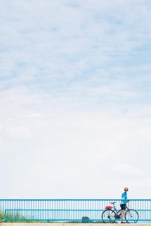ciclo del agua: Fondo para el cartel publicitario o relativa a las actividades ciclismo  deporte  al aire libre - mujeres ciclistas durante una parada en un puente contra el cielo azul (imagen a color entonado)