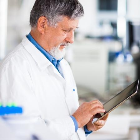 consulting room: Senior doctorscientist using his tablet computer at work (color toned image)