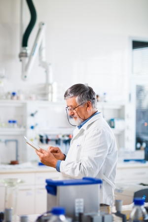Senior doctorscientist using his tablet computer at work   photo