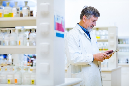 Senior doctorscientist using his tablet computer at work (color toned image) photo