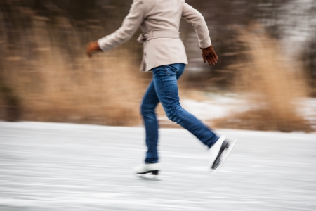 Young woman ice skating outdoors on a pond on a freezing winter day (motion blurred image) photo