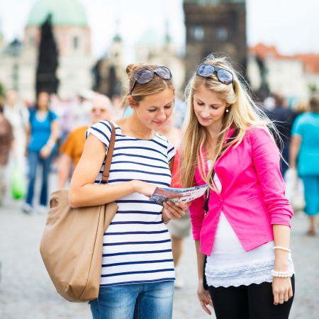 tourist guide: Two female tourists walking along the Charles Bridge while sightseeing in Prague, the historical capital of the Czech Republic (color toned image; shallow DOF)