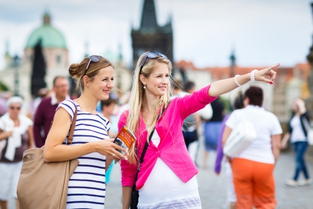 city tourism: Two female tourists walking along the Charles Bridge while sightseeing in Prague, the historical capital of the Czech Republic (color toned image; shallow DOF)