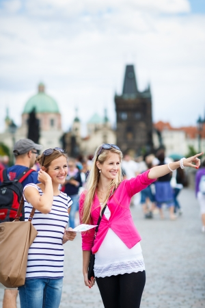 Two female tourists walking along the Charles Bridge while sightseeing in Prague, the historical capital of the Czech Republic (color toned image; shallow DOF) Stock Photo - 17134371