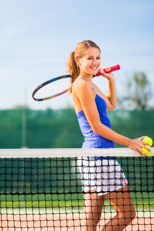 Portrait of a pretty young tennis player with copyspace photo