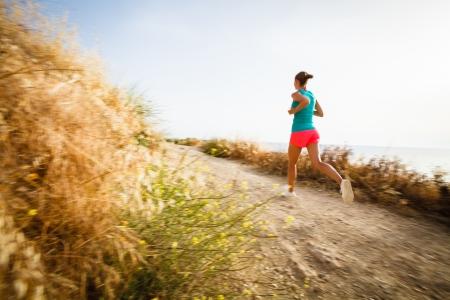 course � pied: Jeune femme sur sa soir�e jogging le long de la c�te