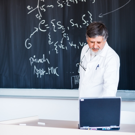 lecturing: Senior chemistry professor writing on the board while having a chalk and blackboard lecture (shallow DOF; color toned image)