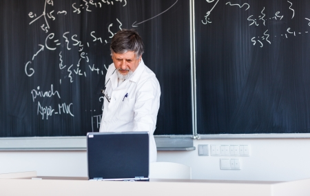 Senior chemistry professor writing on the board while having a chalk and blackboard lecture   photo
