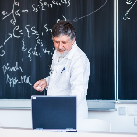 Senior chemistry professor writing on the board while having a chalk and blackboard lecture (shallow DOF; color toned image) photo