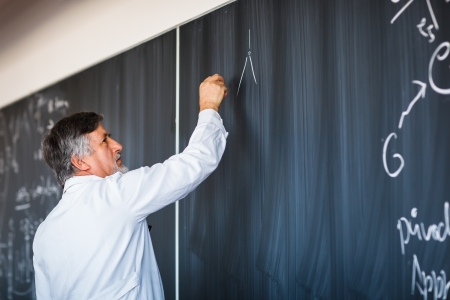 prof: Senior chemistry professor writing on the board while having a chalk and blackboard lecture   Stock Photo