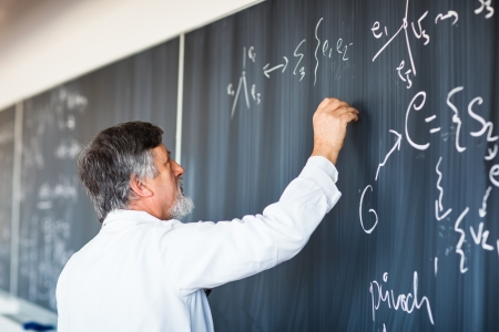 professors: Senior chemistry professor writing on the board while having a chalk and blackboard lecture   Stock Photo