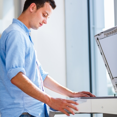 Handsome  young man using a copy machine (shallow DOF; color toned image) Stock Photo - 17134346