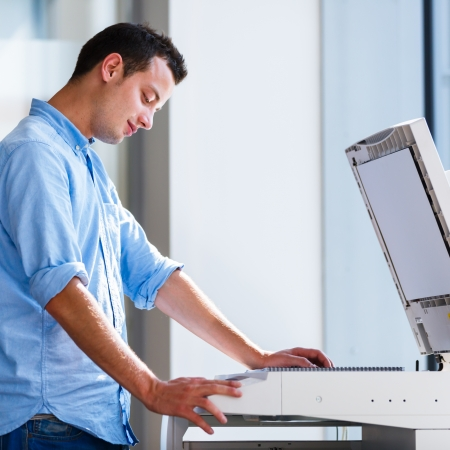 copy machine: Handsome  young man using a copy machine (shallow DOF; color toned image) Stock Photo